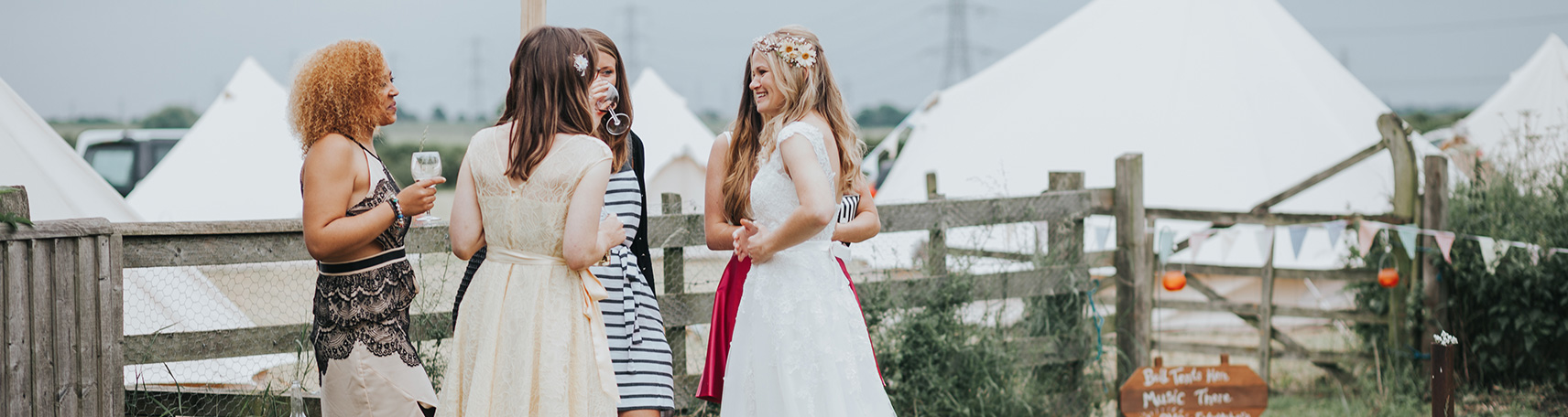 Ladies drinking wine at a bell tent wedding event